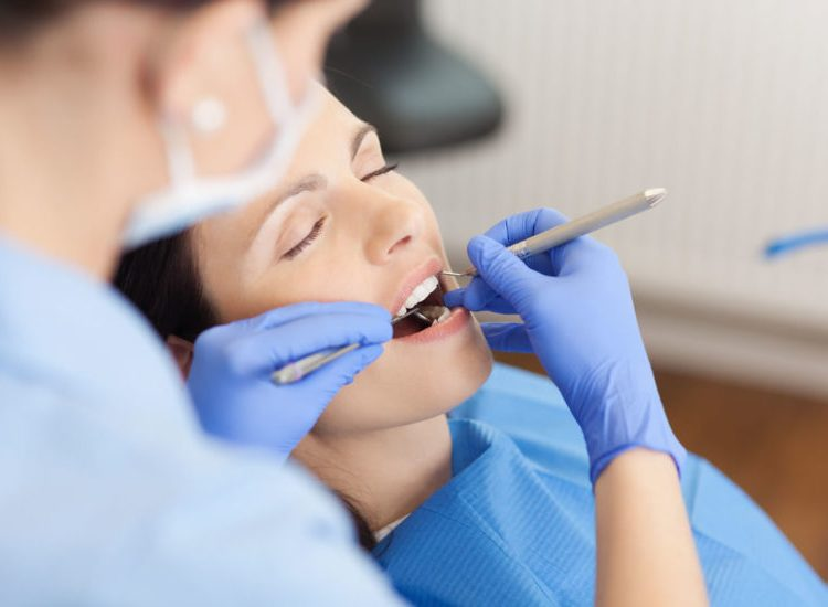 a dental assistant holding a dental hygiene tool while a patient is under sedation